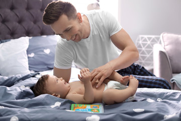 Young father with his cute little son on bed