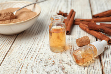 Bottles with cinnamon essential oil on wooden table