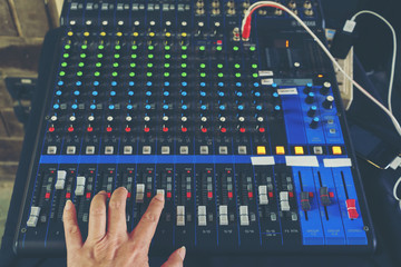 Hand adjusting sound mixer control panel for combining sounds