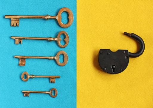 five different golden vintage keys on blue felt and open padlock