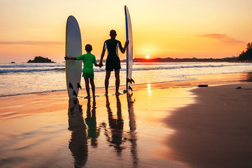 Father and son surfers meet a sunset on the ocean beach