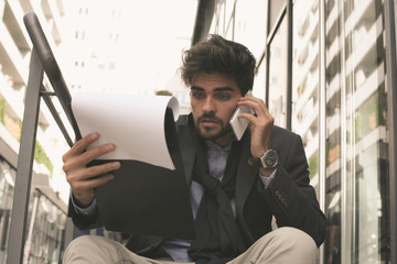 Worried business man on street having serious conversation on mobile and holding document.