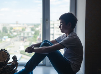 Serious asian boy teen sitting on window with city view
