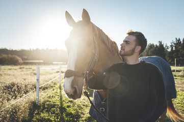 Horse man looking with affection to his horse in the field at sunrise