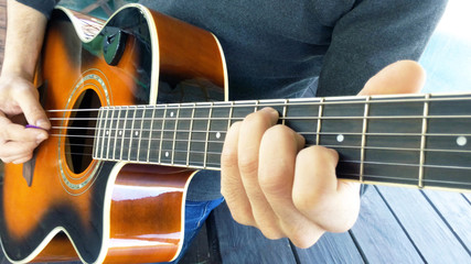 Acoustic guitar. A man plays an guitar with two hands close-up picture