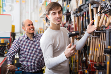 Two men are choosing hammer at tooling section