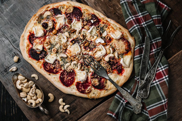 Vegetarian pizza with beetroot on wood background.