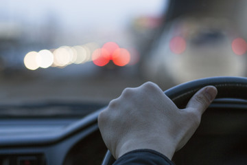 A man drives a car along a city road. Male hand on the wheel close-up