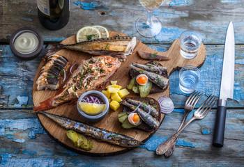 Smoked fish appetizers with mackerel, sturgeon, perch on woden cutting board