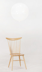 Big White Balloon Hold on Modern Wooden Chair in White Studio