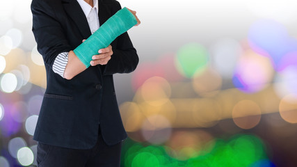 Injured businesswoman with green cast on hand and arm on blurred background bokeh light
