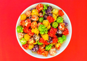 Bowl of colored popcorn on a red background. Top view.