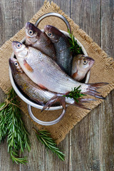 A pile of fresh raw fish with spices, lemon, rosemary on a wooden background. Fresh catch.