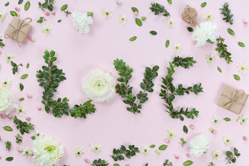 Top view of word Love made of flowers and leaves on white pink background, flat lay concept.