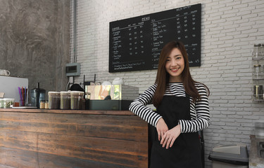 Young woman owner of a cafe stand in front of coffee counter, young entrepreneur conceptual, lifestyle of alpha generation - young successer