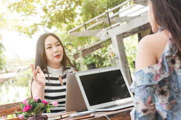 Two teenage women meet in coffee shop use laptop together in afternoon, life style of new teenager, senior mentoring to junior