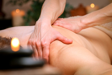 Massage therapist massaging shoulders and back of a male