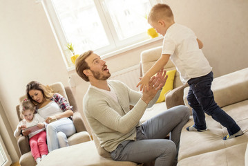 Parents with children playing together and having fun in living room