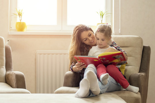 Mother and daughter reading book and having fun while spending time together at home