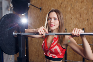 Portrait of young athlete in sports clothes with barbell
