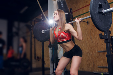 Picture of sports woman squatting with bar