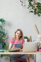 Photo of smiling floral woman with notepad at table with laptop
