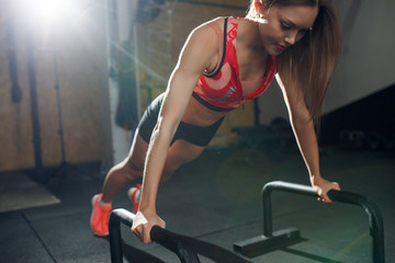 Portrait of sports woman doing exercise bar