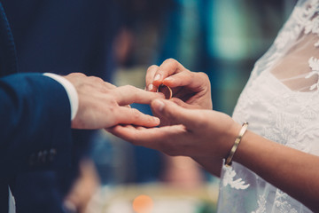 Close-up of bride placing ring on finger of bridegroom at wedding