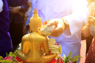 Close-up hand pouring scented water onto buddha statue thai traditional belive for pray and prosperity in Songkran water festival at Thailand.