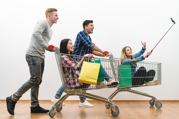The happy people ride on the cart and make a selfie on a white wall background
