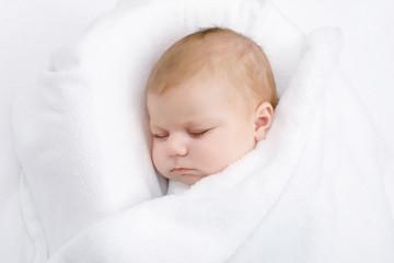 Cute little newborn baby girl sleeping wrapped in blanket