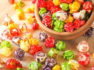 Multi-colored popcorn on a wooden table.