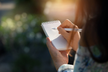 Hand writing on note pad.Woman with long hair hands holding  blanknote writing with white pen  relaxing  by the pool at sunset ,water bokeh  background.