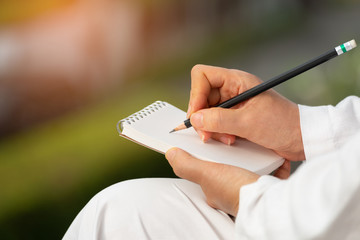 Hand writing on note pad.Woman hands holding  blank note  writing with black pencil relaxing in garden backyard at sunrise ,natural blurred background.