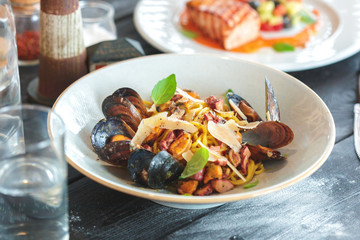 Fresh salad with mussels on a wooden table.