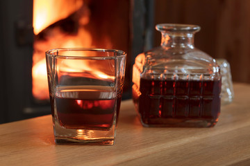 Glass of hard liquor in front of the fireplace.