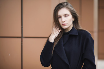 Beautiful girl in a coat in business downtown
