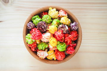 Colored popcorn in a wooden background.