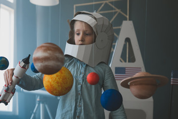 Cute little girl wearing cardboard astronaut helmet flying toy rocket through planets, cardboard spaceship rocket in the background