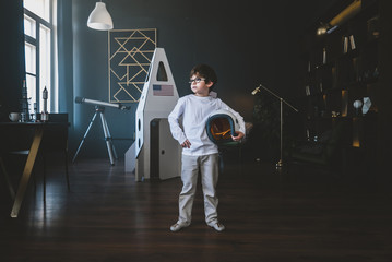 Cute little dreamer boy posing with a helmet at home, pretending to be an astrounaut, cardboard space rocket in the background