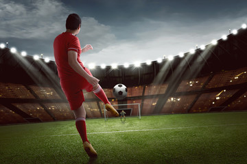 Attractive asian football player shooting the ball to goal