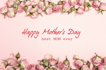 Mothers Day greeting message with small dry roses on pink background. Flat lay, top view