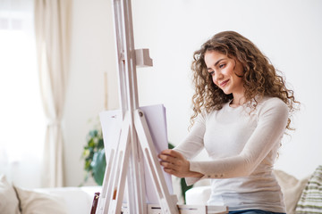 A teenage girl painting a picture at home.
