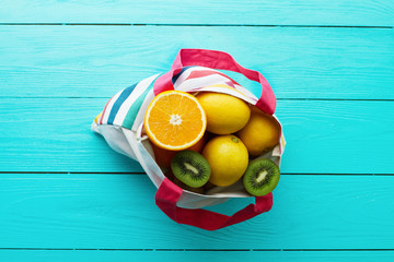 Summer holidays. Fun time. Fruits on blue wooden background. Mock up and picturesque. Orange, lemon, kiwi fruit in bag on table. Top view and mock up. Selective focus