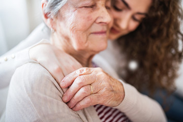 A teenage girl with grandmother at home, hugging.