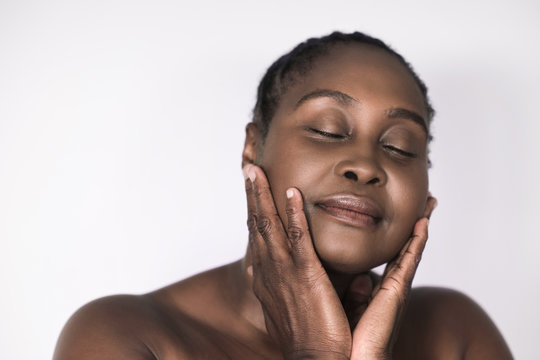 Mature African woman touching her cheeks against a white background