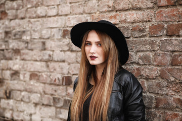 Young beautiful girl in a hat and with a dark make-up outside. G