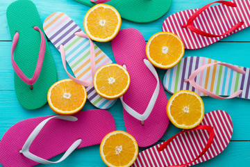 Summer fun time, flip flops. Slippers and orange fruit on blue wooden background. Mock up. Top view. Sandals