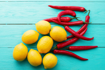 Lemon red, pepers on blue wooden kitchen background. Copy space and mock up