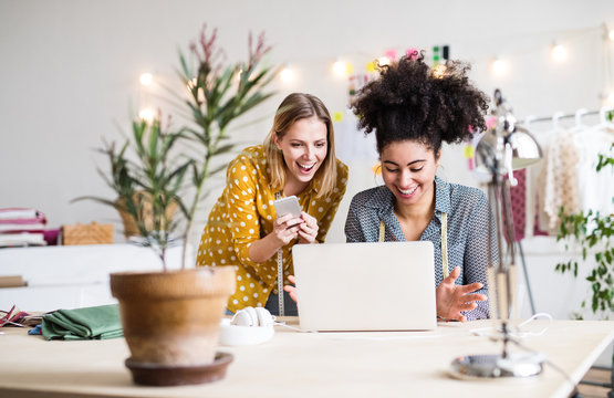 Young creative women with laptop in studio, startup business.